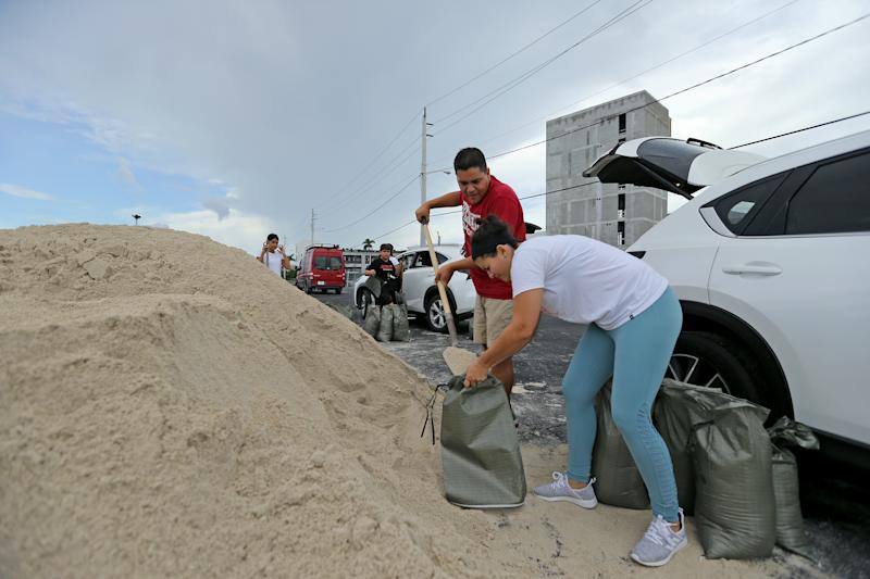 Farah and Max Cicardini fill sand bags at the parking of the Big Easy Casino on Friday, Aug. 30, 2019 in Hallandale Beach, Fla., as they prepare for Hurricane Dorian.