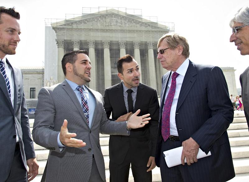 In this photo taken June 20, 2013, California's Proposition 8 same-sex marriage ban paintiffs, Jeff Zarrillo, and Paul Katami, respectively second and third from left, talk to their attorney Ted Olson, center-right, outside the Supreme Court as they leave after the court heard arguments on their case. Sometime this early July, the Court will announce the outcomes in cases, Proposition 8, and the federal Defense of Marriage Act, a federal law that defines marriage as the union of a man and a woman. At left is Adam Umhoefer, executive director of the American Foundation for Equal Rights. (AP Photo/J. Scott Applewhite, File)