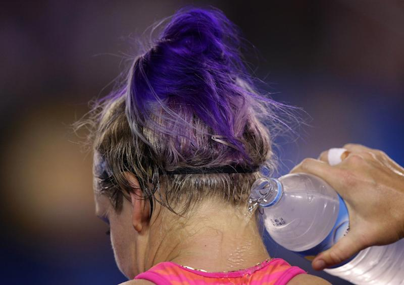 Bethanie Mattek-Sands of the U.S. pours water to her neck as she sits in her chair between games during her first round match against Maria Sharapova of Russia at the Australian Open tennis championship in Melbourne, Australia, Tuesday, Jan. 14, 2014.(AP Photo/Aaron Favila)