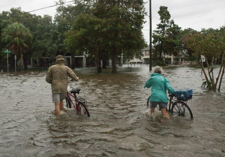 A couple walks their bikes through a flooded street after major storm Barry came ashore in Mandeville, Louisiana on July 14, 2019