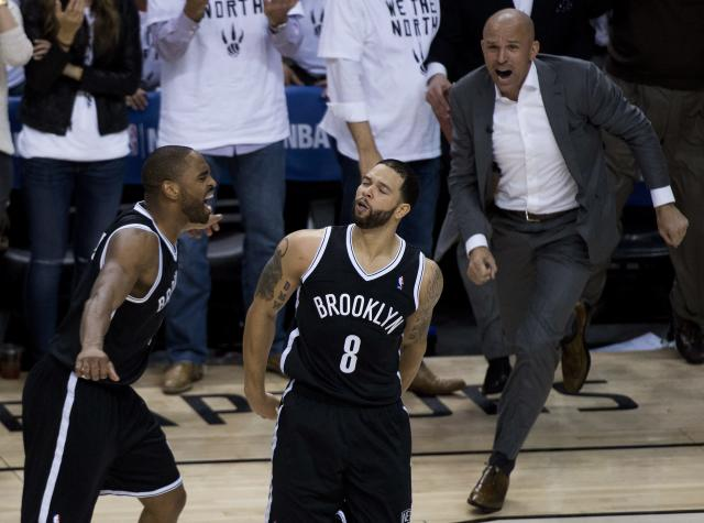 Brooklyn Nets teammates Alan Anderson, left, Deron Williams (8) and head coach Jason Kidd, right, react after they defeated the Toronto Raptors in Game 7 of the opening-round NBA basketball playoff series in Toronto, Sunday, May 4, 2014. (AP Photo/The Canadian Press, Nathan Denette)