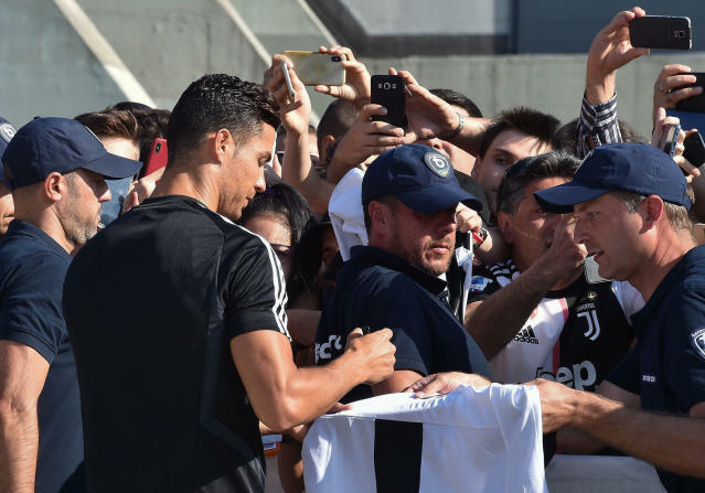 Juventus' Cristiano Ronaldo signs autographs as he arrives at the team's medical center before taking part to a training session, in Turin, Italy, Saturday, July 13, 2019. (Alessandro Di Marco/ANSA via AP)