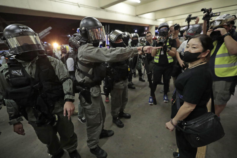 Police in riot gear ask a woman to take off her mask outside a train station in Hong Kong, Sunday, Nov. 3, 2019. Riot police stormed several malls in Hong Kong on Sunday in a move to thwart more pro-democracy protests, as the city's leader heads to Beijing for talks on deepening economic integration between the semi-autonomous Chinese territory and mainland China. (AP Photo/Dita Alangkara)