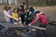 Children from Brooklyn Apple Academy roast marshmallows on a fire they made in a barbecue area as instructor and co-owner Noah Mayers, rear, hands out marshmallows Thursday, Jan. 14, 2021, at Brooklyn's Prospect Park in New York. (AP Photo/Kathy Willens)