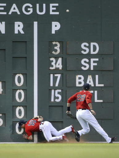 Boston Red Sox center fielder Andrew Benintendi (16) crashes into the wall as left fielder J.D. Martinez (28) chases down an RBI double by Seattle Mariners' Denard Span during the fourth inning of a baseball game at Fenway Park, Friday, June 22, 2018, in Boston. (AP Photo/Elise Amendola)