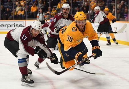 Nov 27, 2018; Nashville, TN, USA; Nashville Predators right wing Ryan Hartman (38) is tripped by Colorado Avalanche center Tyson Jost (17) as he battles for a puck during the third period at Bridgestone Arena. Mandatory Credit: Christopher Hanewinckel-USA TODAY Sports