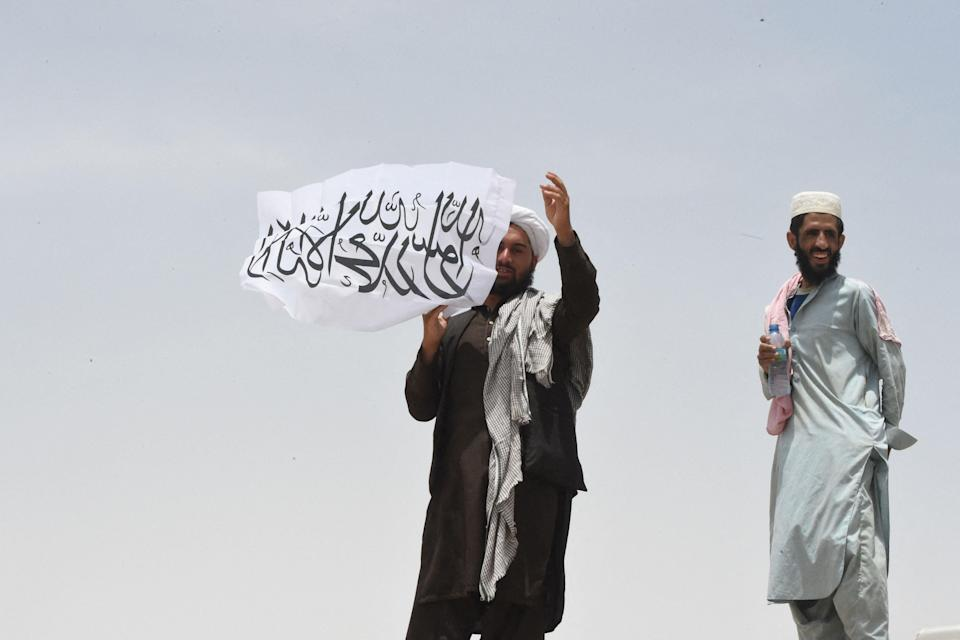 A man standing on the Afghan side of the border holds a Taliban flag near a crossing point in Pakistan (AFP/Getty)
