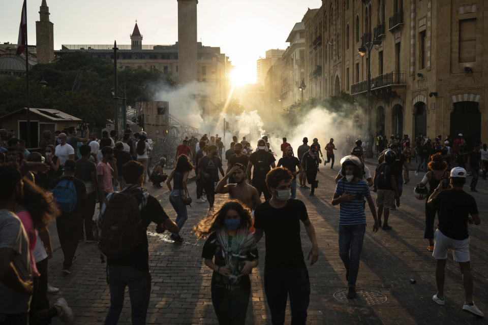 Demonstrators run from tear gas fired by police near the parliament building during a protest against the political elite and the government following last Tuesday's deadly explosion at the Beirut port which devastated large parts of the capital, in Beirut, Lebanon, Sunday, Aug. 9, 2020. (AP Photo/Felipe Dana)