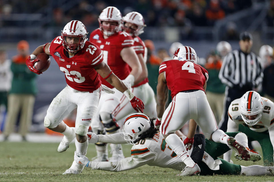 Wisconsin running back Jonathan Taylor (23) breaks a tackle by Miami defensive back Romeo Finley (30) during the first half of the Pinstripe Bowl NCAA college football game Thursday, Dec. 27, 2018, in New York. Wisconsin defeated Miami 35-3. (AP Photo/Adam Hunger)