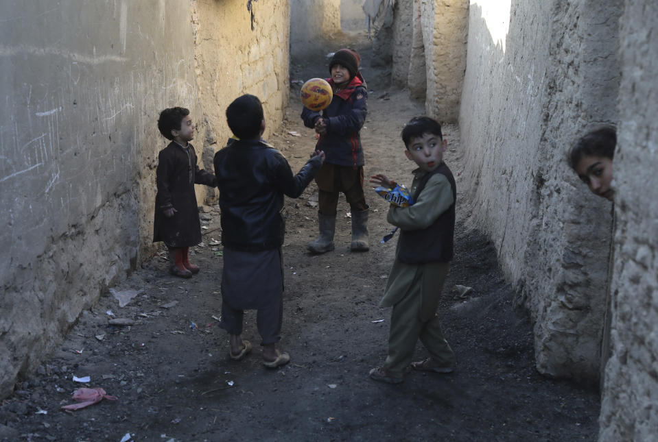 Internally displaced boys play with a ball outside their temporary home in the city of Kabul, Afghanistan, Wednesday, Dec. 30, 2020. Save the Children has warned that more than 300,000 Afghan children face freezing winter conditions that could lead to illness, in the worst cases death, without proper winter clothing and heating. (AP Photo/Rahmat Gul)