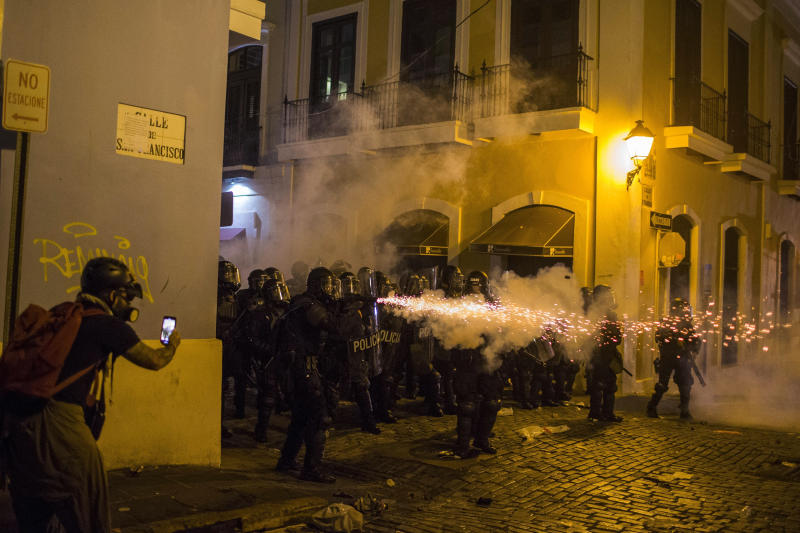 A policeman shoots tear gas during clashes near the executive mansion demanding the resignation of Gov. Ricardo Rossello, in San Juan, Puerto Rico, Wednesday, July 17, 2019. (Photo: Dennis M. Rivera Pichardo/AP)