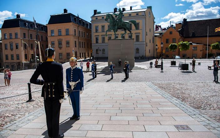 Two soldiers in traditional uniform perform the changing of guards outside the Royal Palace in Stockholm, Sweden, 22 July 2020 - Ali Lorestani/TT/EPA-EFE/Shutterstock