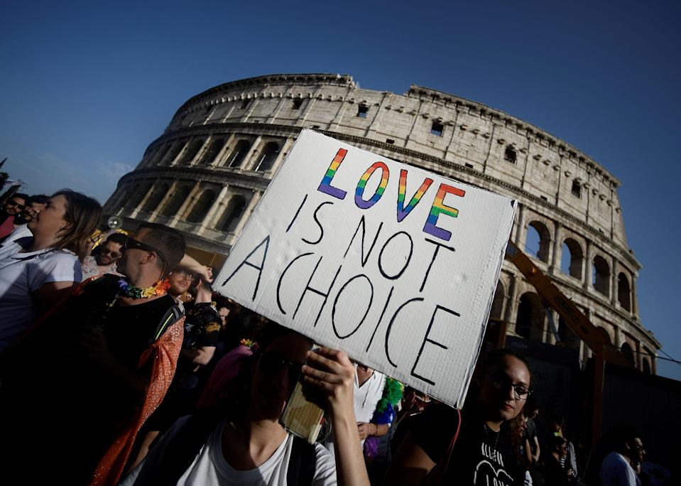 Participants walk past the Colosseum monument in Rome during the annual Gay Pride parade (AFP via Getty Images)