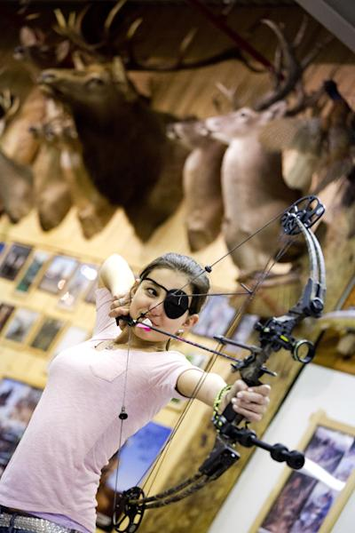 """In this April 13, 2012 photo, Nicole Donzella of Fair Lawn, N.J., 15, participates in the youth archery league at Targeteers Archery in Saddle Brook. In schools and backyards, for their birthdays and out with their dads, kids are gaga for archery a month after the release of """"The Hunger Games."""" Archery ranges around the country have enjoyed a steady uptick among kids of both sexes in the movie's lead-up, though 16-year-old heroine Katniss Everdeen, the archery ace seems to resonate with girls more than boys. Donzella uses an eye patch to help line up her target. (AP Photo/Charles Sykes)"""