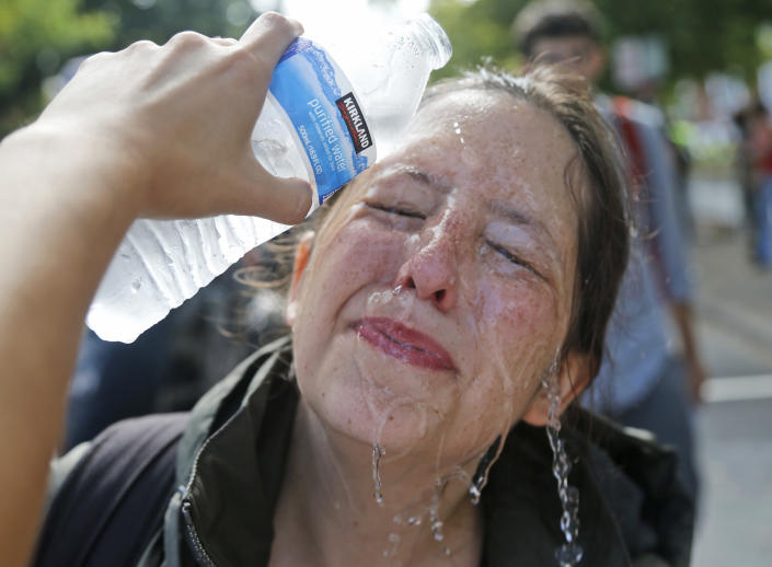 <p>A counter demonstrator gets a splash of water after being hit by pepper spray at the entrance to Lee Park in Charlottesville, Va., Saturday, Aug. 12, 2017. (Photo: Steve Helber/AP) </p>