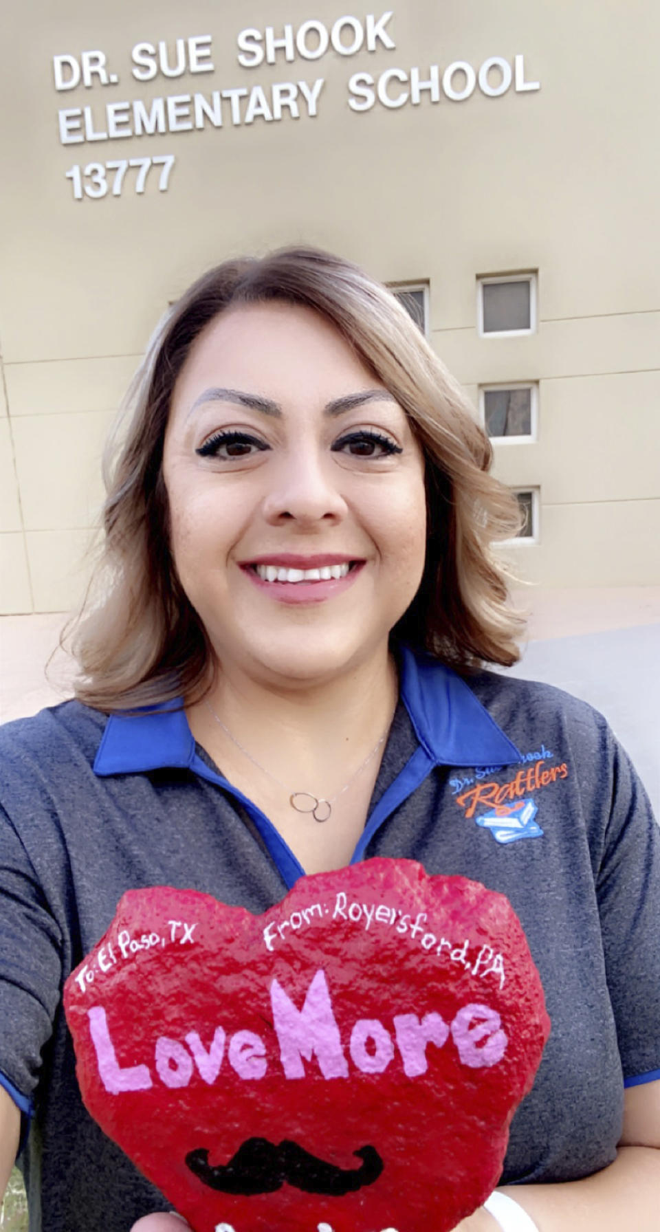 """In this Aug. 2, 2021, photo provided by Monica Aguilera, Aguilera takes a selfie with a heart-shaped """"kindness rock"""" memorializing Texas teacher Zelene Blancas, who died of COVID-19 in December 2020, outside of Dr. Sue A. Shook Elementary School in El Paso, Texas. (Monica Aguilera via AP)"""