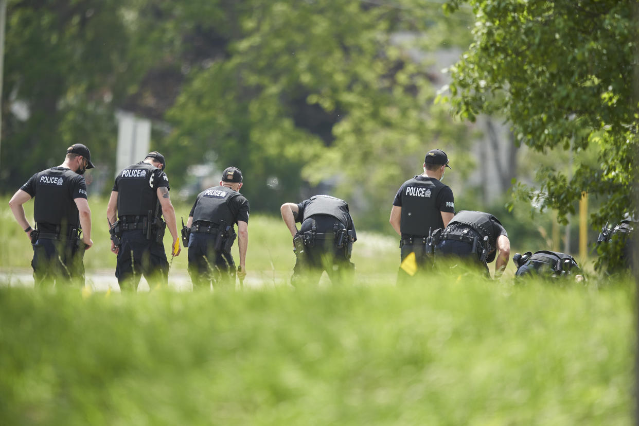 A line of police officers look for evidence at the scene of a car crash in London, Ontario on Monday, June 7, 2021. Police say multiple people have died after several pedestrians were struck by a car Sunday night. (Geoff Robins/The Canadian Press via AP)