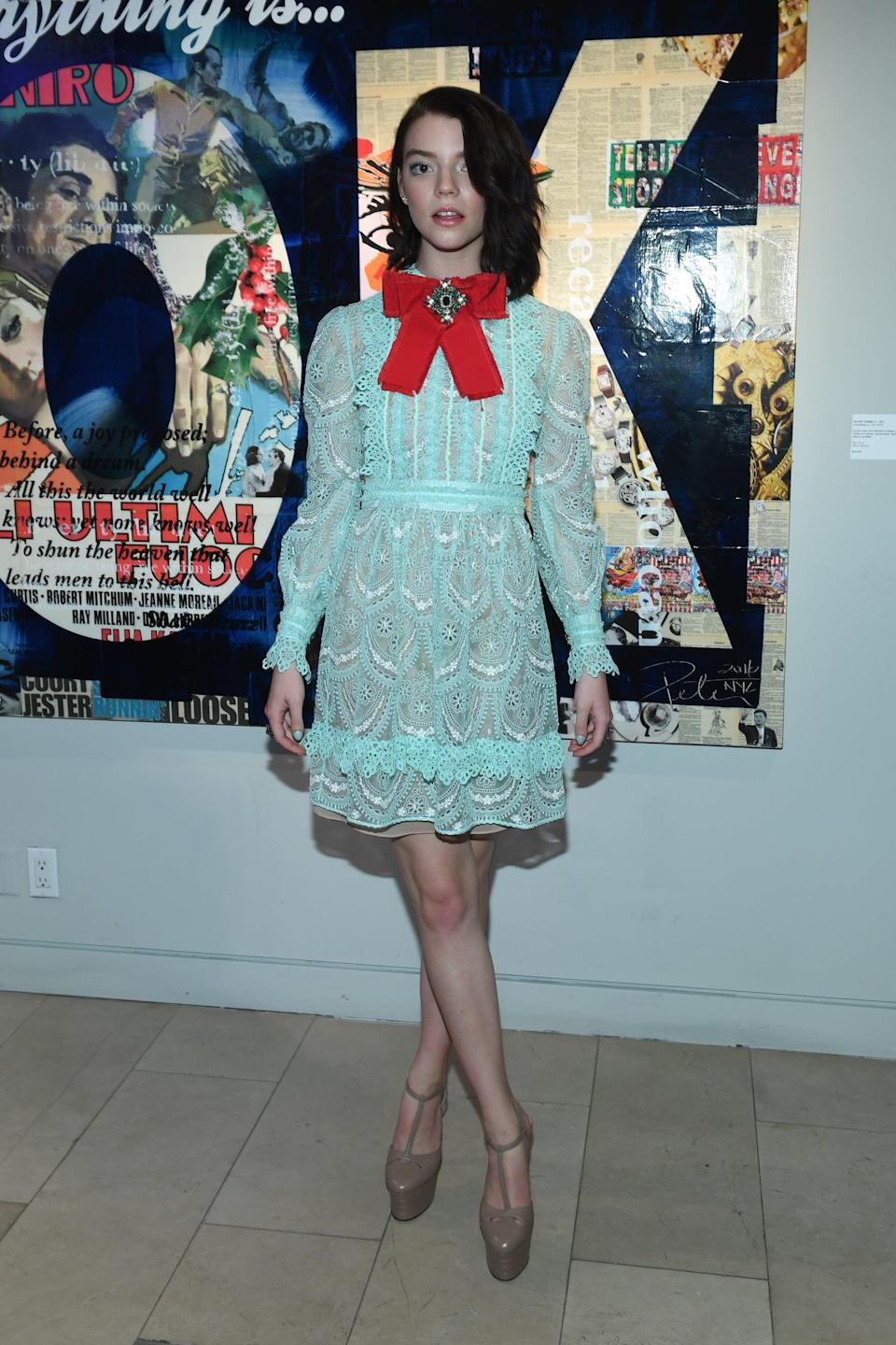 <p>Anya wore a turquoise lace Gucci dress with a red bow at the neck.</p>