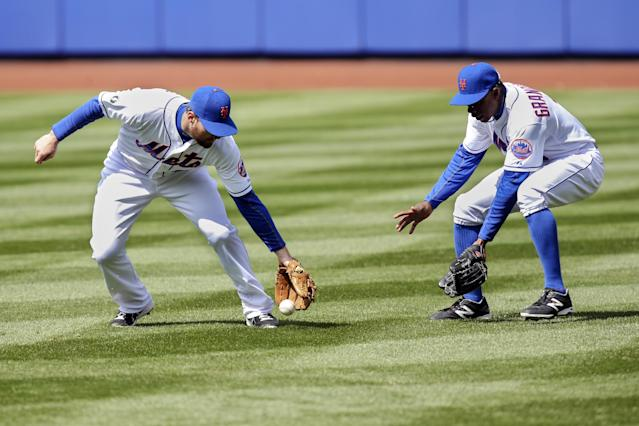 New York Mets second baseman Daniel Murphy, left, makes an error on a fly ball alongside right fielder Curtis Granderson in the fifth inning of a baseball game against the Cincinnati Reds at Citi Field, Saturday, April 5, 2014, in New York. (AP Photo/John Minchillo)