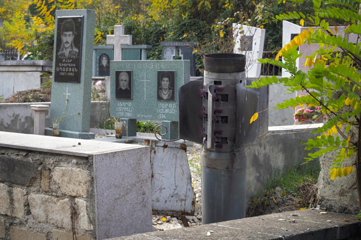 A tail of a multiple rocket 'Smerch' sticks out in a tomb at a cemetery, after shelling by Azerbaijan's artillery in Stepanakert, the separatist region of Nagorno-Karabakh, Tuesday, Nov. 3, 2020. Fighting over the separatist territory of Nagorno-Karabakh entered sixth week on Sunday, with Armenian and Azerbaijani forces blaming each other for new attacks. (AP Photo)