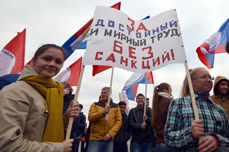 """Protesters hold a poster reading """"For decent and peaceful labour without sanctions!"""" during a rally in the Russian city of Stavropol, on October 7, 2014 (AFP Photo/Danil Semyonov)"""