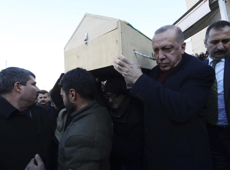 Turkey's President Recep Tayyip Erdogan carries a coffin of a victim after an earthquake hit Elazig, eastern Turkey, Friday, during the funeral procession for Salih Civelek and Aysegul Civelek, Saturday, Jan. 25, 2020. Rescue workers were continuing to search for people buried under the rubble of apartment blocks in Elazig and neighbouring Malatya. Mosques, schools, sports halls and student dormitories were opened for hundreds who left their homes after the quake (Presidential Press Service via AP, Pool)