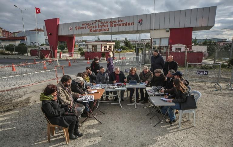 This picture taken and released by the Cumhuriyet daily newspaper on December 15, 2015 shows Cumhuriyet's journalists doing their editorial news meeting next to the Silivri prison, to demonstrate their support for their jailed editor in-chief