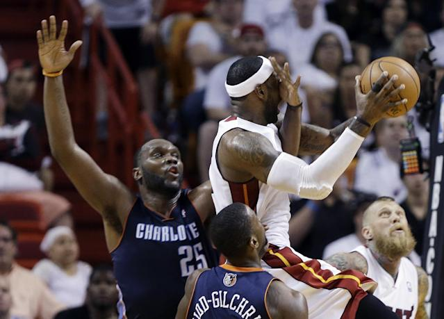 Miami Heat's LeBron James, center, goes up to shoot as Charlotte Bobcats' Al Jefferson's hand is in front of his face during the second half in Game 2 of an opening-round NBA basketball playoff series, Wednesday, April 23, 2014, in Miami. The Heat defeated the Bobcats 101-97. (AP Photo/Lynne Sladky)