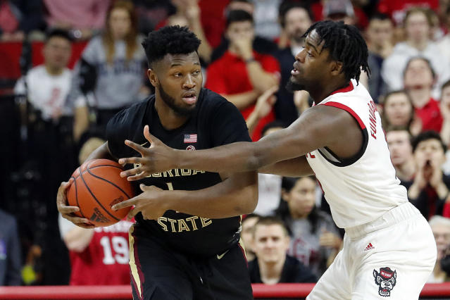 North Carolina State's DJ Funderburk, right, battles with Florida State's RaiQuan Gray (1) for the ball during the first half of an NCAA college basketball game in Raleigh, N.C., Saturday, Feb. 22, 2020. (AP Photo/Karl B DeBlaker)