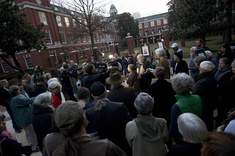 Supporters, reporters, and family gather around Michele Naar-Obed as she makes a statement concerning the sentencing of her husband Greg Boertje-Obed and two others for the role they played in a July 2012 break-in at the Y-12 National Security Complex in Knoxville, Tenn., Tuesday, Feb. 18, 2014. Sister Megan Rice, 84, was sentenced to nearly three years in prison and Michael Walli and Greg Boertje-Obed were sentenced to more than five years in prison. The break-in raised questions about the safekeeping at the facility that holds the nation's primary supply of bomb-grade uranium. (AP Photo/The Knoxville News Sentinel, Saul Young)