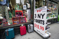 A sign announcing a special on T-shirts is placed on the sidewalk outside a gift shop in Lower Manhattan, Tuesday, Nov. 17, 2020. In souvenir shops from Times Square to the World Trade Center, shelves full of T-shirts and trinkets still love New York, as the slogan goes. But the proprietors wonder when their customers will, again. The coronavirus has altered many aspects of life and business in the United States' biggest city, and the pandemic is taking a major toll on the gifts-and-luggage stores that dot tourist-friendly areas. After setting records year after year since 2010, travel to New York has plummeted during the pandemic. (AP Photo/Mary Altaffer)