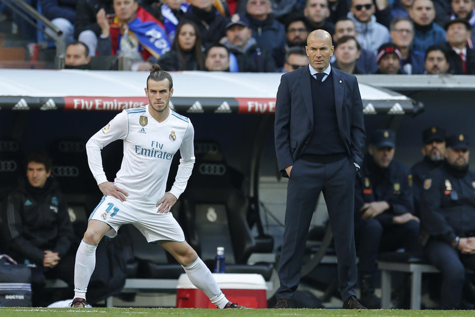 Real Madrid's Gareth Bale stretches next to Real Madrid's head coach Zinedine Zidane while waiting to come on as substitute during a Spanish La Liga soccer match between Real Madrid and Barcelona at the Santiago Bernabeu stadium in Madrid, Spain, Saturday, Dec. 23, 2017. (AP Photo/Paul White)