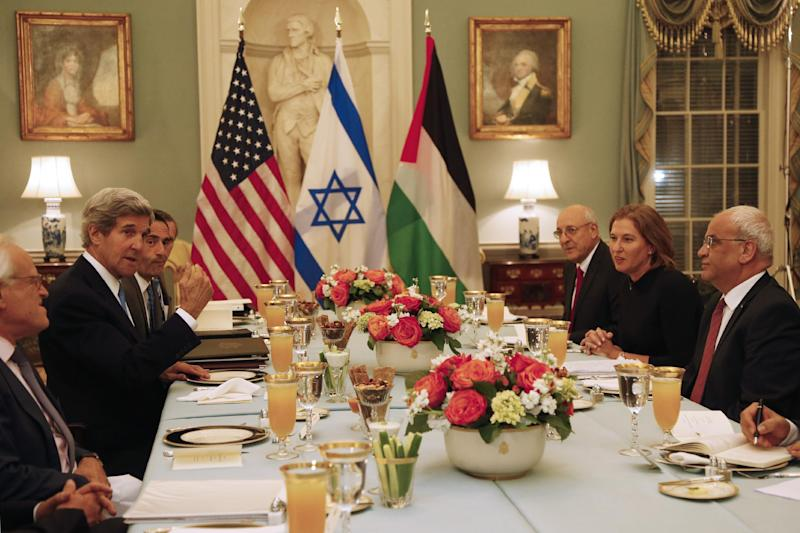 Secretary of State John Kerry, second left, is seated with Israel's Justice Minister and chief negotiator Tzipi Livni, second right, Palestinian chief negotiator Saeb Erekat, right, and Yitzhak Molcho, an adviser to Israeli Prime Minister Benjamin Netanyahu, at an Iftar dinner, which celebrates Ramadan, at the State Department in Washington, marking the resumption of Israeli-Palestinian peace talks, Monday, July 29, 2013. (AP Photo/Charles Dharapak)