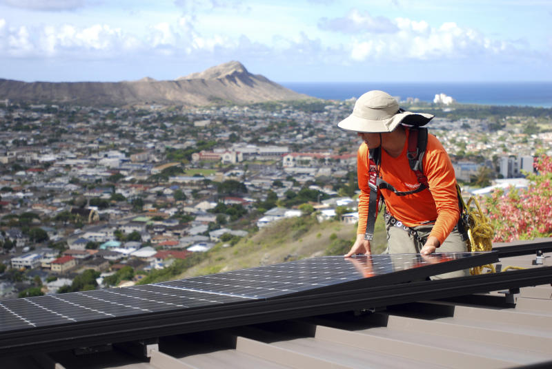 FILE - In this July 8, 2016, file photo, Dane Hew Len, lead installer for RevoluSun, places a solar panel on a roof in Honolulu. If you have the cash, most experts agree buying a solar system outright is a better investment than leasing or taking out a loan. Customers should check electric bills to estimate monthly energy use when deciding what size system to buy, and calculate federal or state incentives. (AP Photo/Cathy Bussewitz, File)
