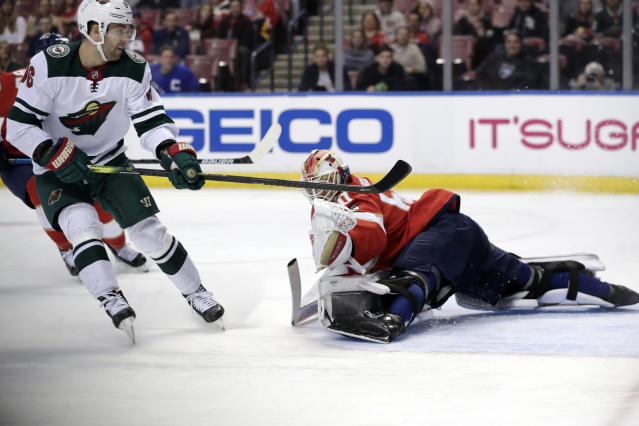 Minnesota Wild left wing Jason Zucker, left, scores a goal past Florida Panthers goaltender Chris Driedger during the second period of an NHL hockey game, Tuesday, Dec. 3, 2019, in Sunrise, Fla. (AP Photo/Lynne Sladky)