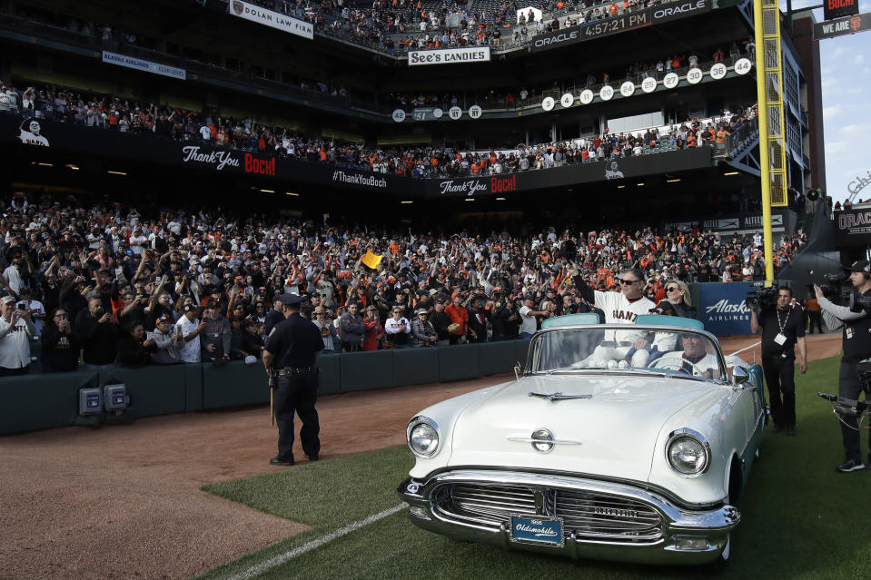 San Francisco Giants manager Bruce Bochy, seated in car at left, is driven around the field with his wife Kim during a ceremony honoring Bochy after a baseball game between the Giants and the Los Angeles Dodgers in San Francisco, Sunday, Sept. 29, 2019. (AP Photo/Jeff Chiu, Pool)