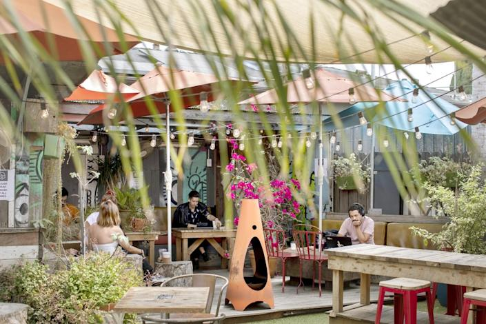 People sit at tables in an outdoor seating area with plants.