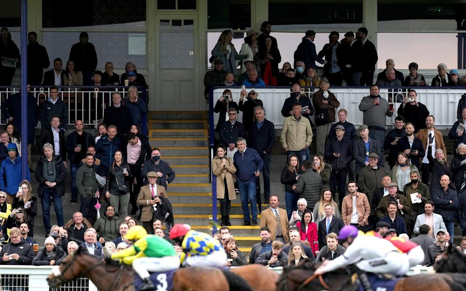 Spectators watch from the stands as Stake Acclaim (left) ridden by Callum Hutchinson comes home second in the Fitzdares Loves Royal Windsor Racecourse Handicap - John Walton - Pool/Getty Images