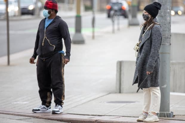 Masked pedestrians wait at an intersection in downtown Ottawa in May 2021.