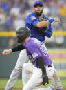 Chicago Cubs second baseman David Bote, back, forces out Colorado Rockies' Trevor Story at second base on the front end of a double play hit into by C.J. Cron to end the third inning of a baseball game Wednesday, Aug. 4, 2021, in Denver. (AP Photo/David Zalubowski)