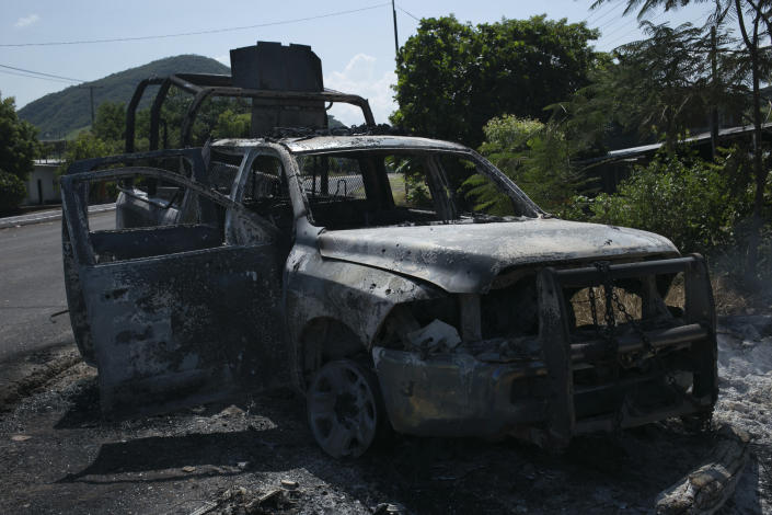 A charred truck that belong to Michoacan state police stands on the roadside after it was burned during an attack in El Aguaje, Mexico, Monday, Oct. 14, 2019. At least 13 police officers were killed and three others injured Monday in the ambush. (AP Photo/Armando Solis)