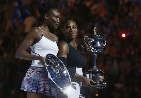 Serena Williams holds her trophy after winning her final match against Venus Williams of the U.S. REUTERS/Thomas Peter