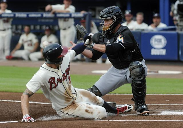 Miami Marlins catcher Koyie Hill, right, can't stop Atlanta Braves' Jordan Schafer, from scoring on a sacrifice fly by Freddie Freeman during the first inning of a baseball game, Saturday, Aug. 31, 2013, in Atlanta. (AP Photo/John Amis)