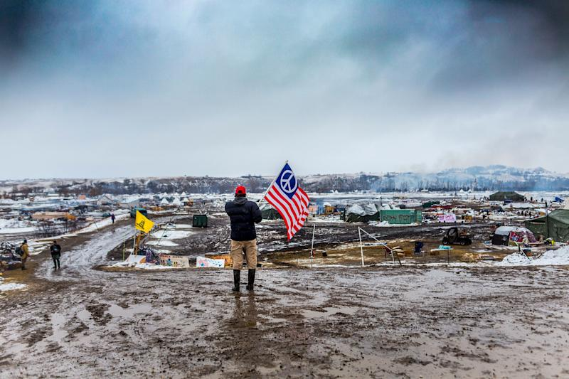 A defiant Dakota Access pipeline protester faces off against militarized police in 2017 as law enforcement raided their camp. (Photo: Pacific Press via Getty Images)