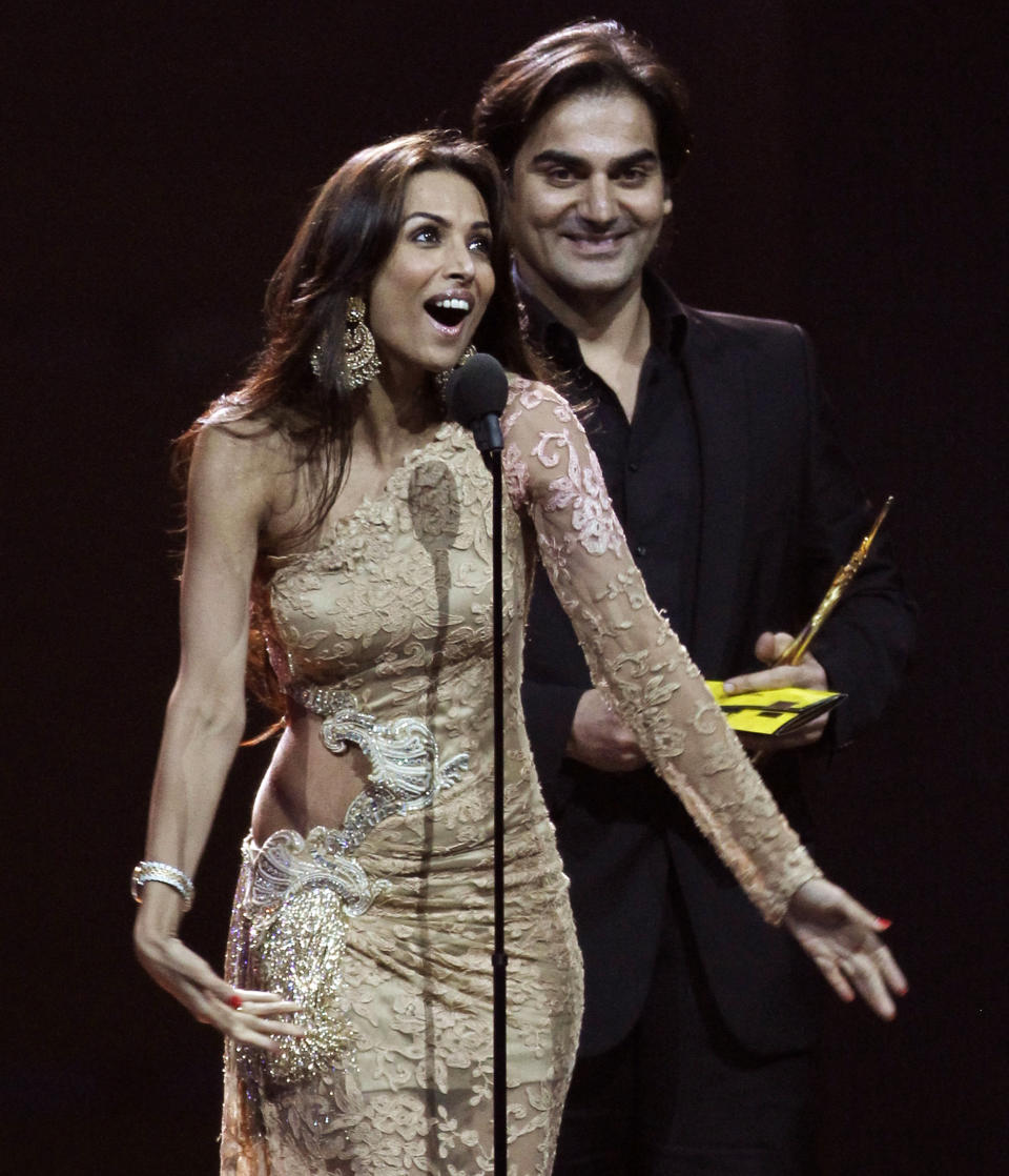 "Arbaaz Khan accepts his award for best picture for his work in ""Dabangg"" as his wife Malaika Arora-Khan talks during the International Indian Film Academy (IIFA) awards show in Toronto June 25, 2011. REUTERS/Mark Blinch (CANADA - Tags: ENTERTAINMENT)"