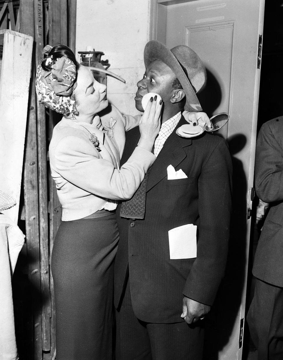 <p>The comedian and actor wore a black pinstripe suit, checkered button-down, and felt fedora for a CBS Christmas radio show. He received a touch-up from singer Carmen Miranda during a break, who was also performing on the holiday broadcast. </p>