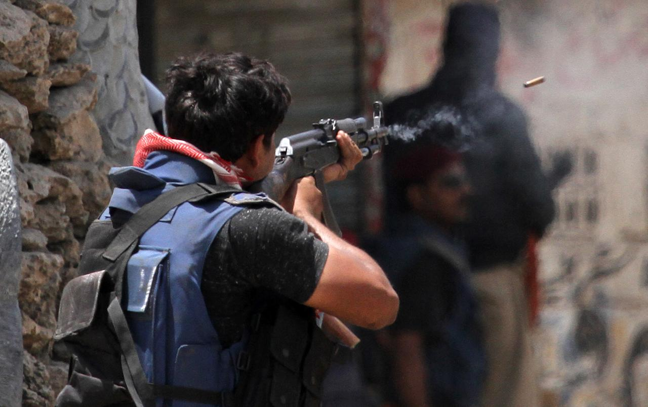 <p>A Pakistani police commando fires at the hideout of alleged criminals during a crackdown operation against criminals in Karachi's town of Lyari in Pakistan, on April 27, 2012. Criminals and police exchanged fire during the action that killed two person and injured many, security official said. (AP Photo/Shakil Adil) </p>