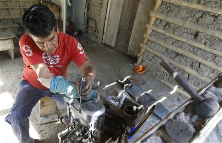 Manuel Bonilla, 62, who lost his right arm when rebels detonated a bus bomb in Toribio's central square, works on a motorcycle engine during a Reuters interview in Toribio