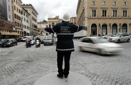 Policeman gestures as he directs traffic in downtown Rome