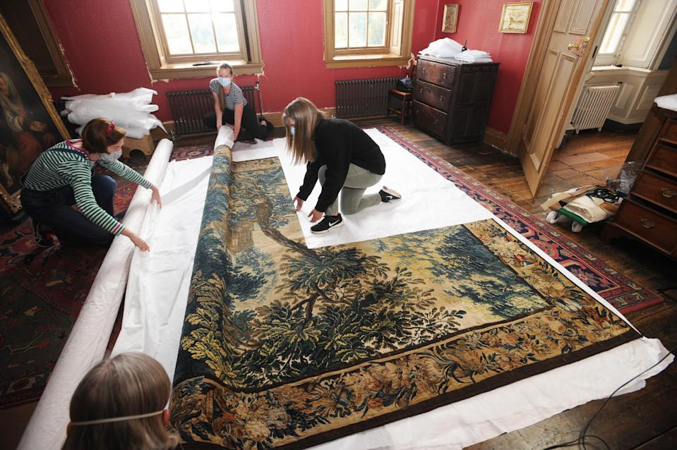 National Trust staff unroll the tapestry ready to rehang it at Dyrham Park (Barry Batchelor/National Trust/PA)